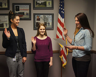 Second-year student Ashley Kelican administers the Air Force oath to first-year students Megan Guyan (left) and Erica Hamman.