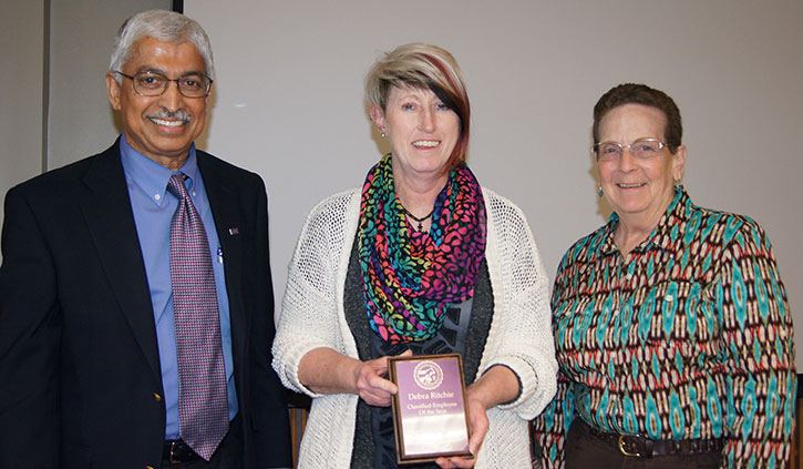 Dr. M.M. Chengappa and Dr. Patricia Payne present Debra Ritchie, center, with the DM/P's Classified Employee of the Year Award.
