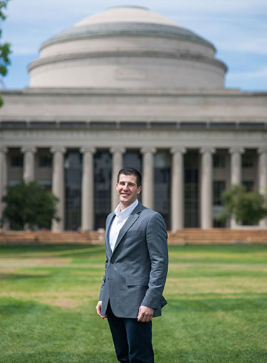 Dustin Aherin stands in front of the Great Dome on the MIT campus.